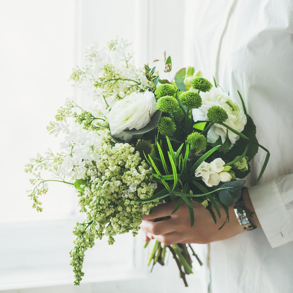Young woman wearing white clothes holding flowers bouquet. Wedding concept